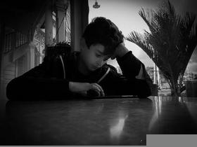 Grainy black and white boy at table in low light in front of window resting  on his elbow concentrating with hand poised